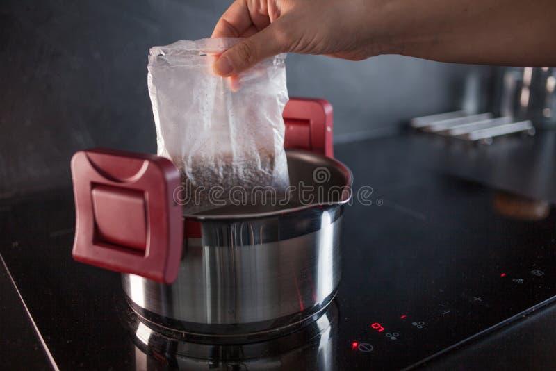 Boekweit in gedeeltezakken voor het koken De kokende boekweithavermoutpap, een vrouw zet een zak voor het koken in een pot stock afbeelding