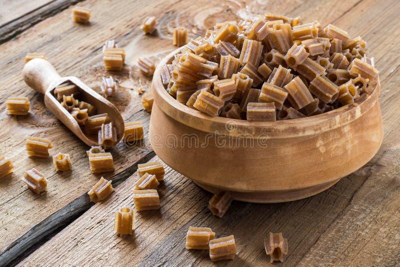 Boekweitdeegwaren in een houten kom stock afbeelding
