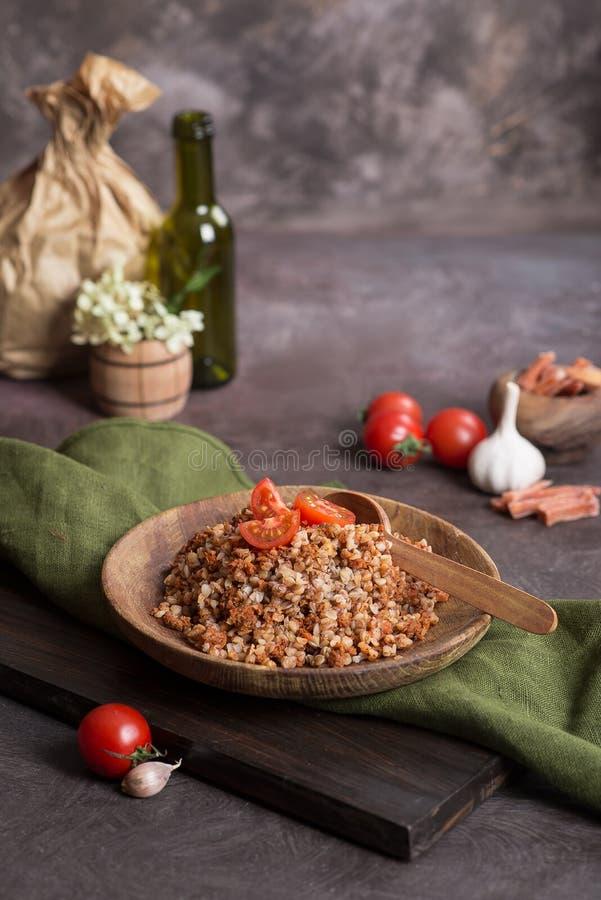 Boekweithavermoutpap met tomaat op een houten plaat royalty-vrije stock fotografie