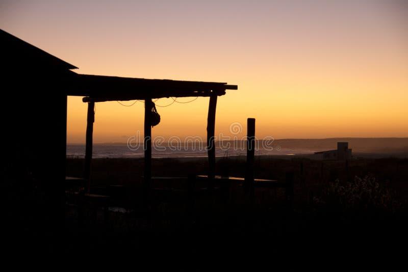 Boerderijhuis bij zonsondergang met overzees royalty-vrije stock afbeeldingen