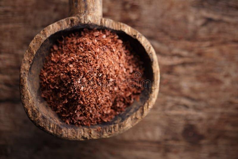 Boete geraspte chocolade in oude houten lepel stock foto