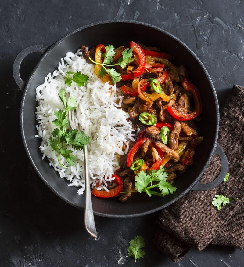 Boeuf épicé avec les légumes et le riz dans une poêle de fonte sur un fond foncé, vue supérieure photos libres de droits