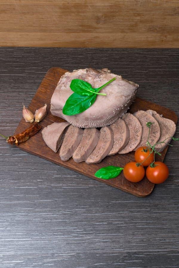 Boeuf bouilli, langue de porc avec des tomates, feuille de basilic, tir de studio, sur le fond en bois images stock
