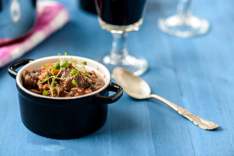 Boeuf bourguignon classic french beef stew on blue table with a. Glass of red wine stock image
