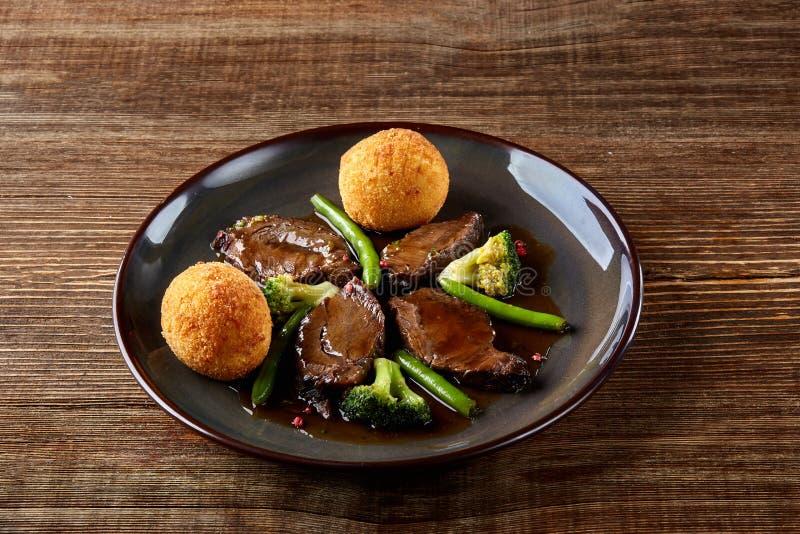 Boeuf cuit avec des légumes sur la fin en bois de fond  Paraboloïdes chauds de viande Vue supérieure photo stock