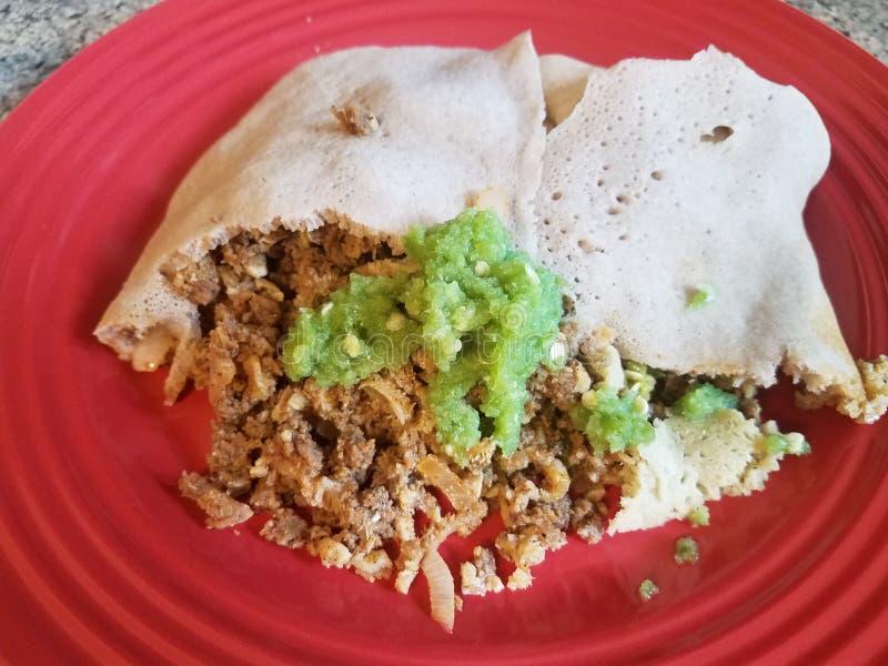 Boeuf de nourriture et pain éthiopien et sauce à poivron vert épicée de plat rouge images stock
