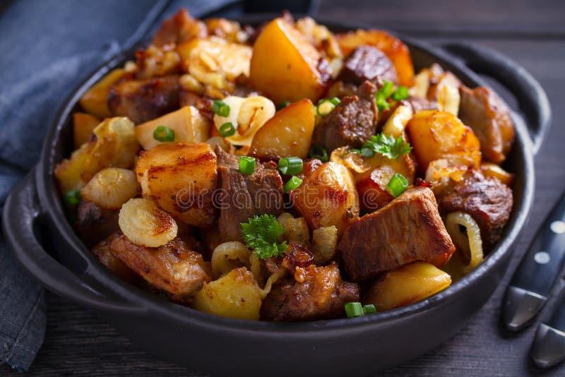 Boeuf et pommes de terre frits aux oignons et à l'ail servis dans le plat noir sur le fond en bois photo libre de droits