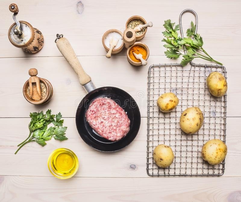 Boeuf haché frais dans une poêle avec une pomme de terre sur le gril pour rôtir, assaisonnant pour des herbes d'hamburgers sur le photos stock
