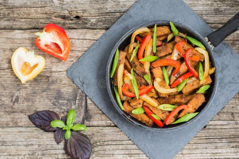 Boeuf sauté avec des légumes dans une casserole Fond en bois Vue supérieure Plan rapproché image stock