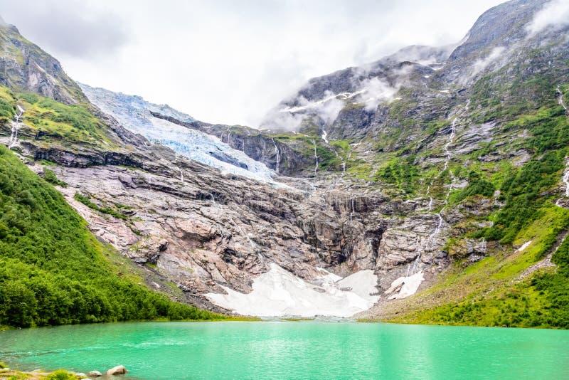 Boeyabreen glaciär i bergen med sjön i förgrunden, Jostedalsbreen nationalpark, Fjaerland, Norge royaltyfria foton