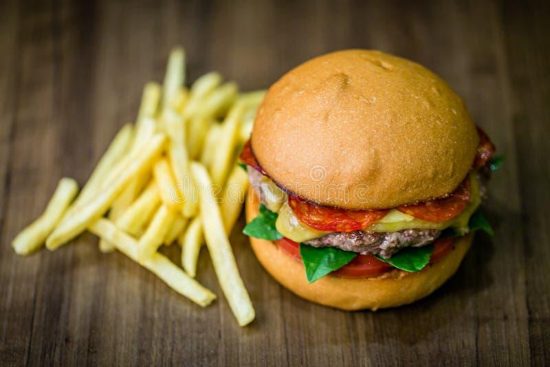 Boftenburger mit Käse, italienische Peroni, Tomaten, Basilikum und Pommes frites auf Holztisch und rustikalem Hintergrund stockfotografie