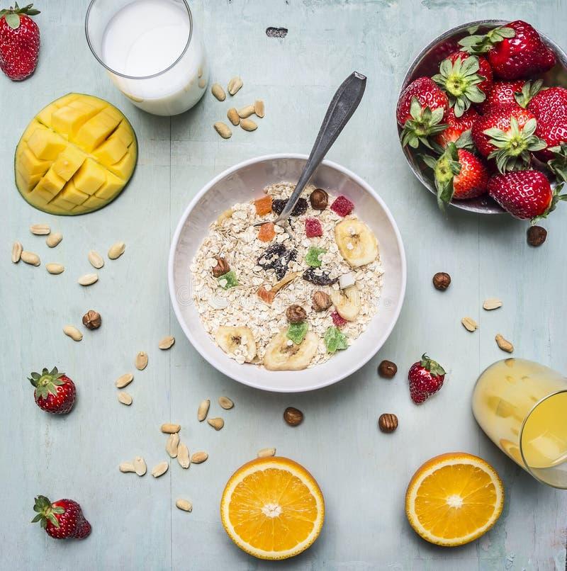Bogactwa śniadanie, oatmeal z, truskawki i mango, dokrętkami i wysuszonymi owoc, świeży sok na drewnianym nieociosanym tło wierzc fotografia royalty free