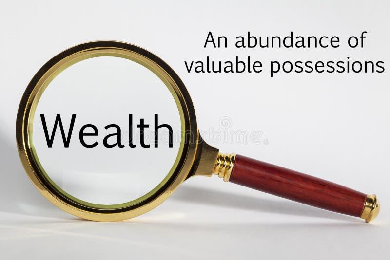 Bogactwa pojęcie z słowami i Powiększać - szkło obrazy royalty free