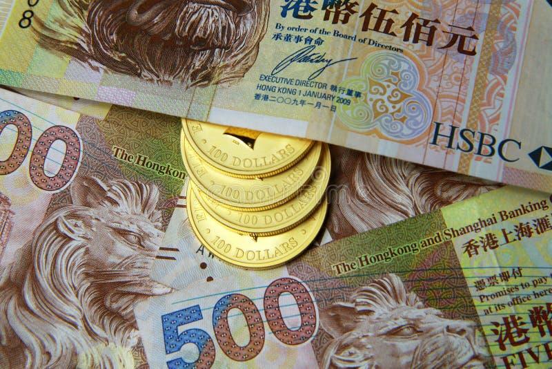 Bogactwo - Złocista moneta i Hong Kong dolar obrazy stock