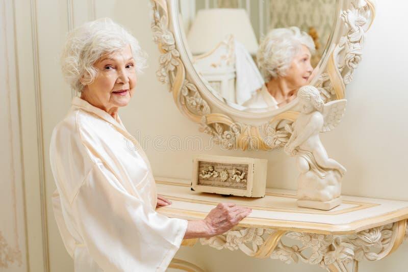 Bogata stara kobieta satysfakcjonuje z jej pojawieniem obraz stock