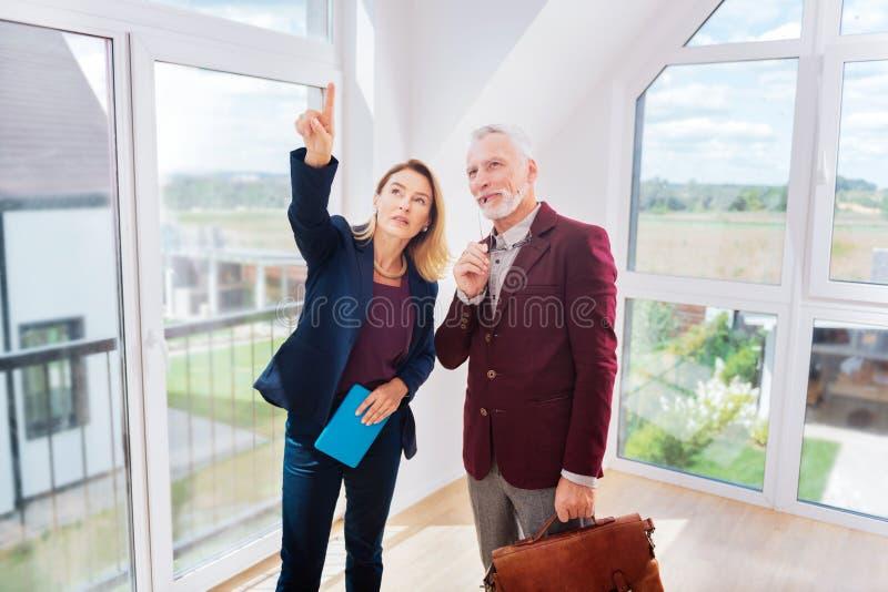 Bogaty biznesmen myśleć o kupienie nowym domu stoi blisko pośrednik w handlu nieruchomościami zdjęcia stock