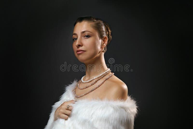 Bogaty styl ?ycia Pi?kna plciowa kobieta jest ubranym jewellery i bia?ego futerkowego kamizelki pi?kno, moda obraz stock