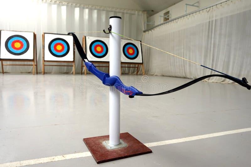 Bogenschießenbogen, der an seinem Stand, mit Zielen im Hintergrund hängt stockbild