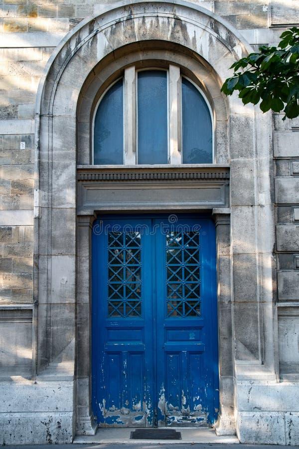Bogentür mit Fenster des Altbaus in Paris Frankreich Hölzerner blauer gemalter Eingang der Weinlese mit abblätternder Farbe stockfotografie