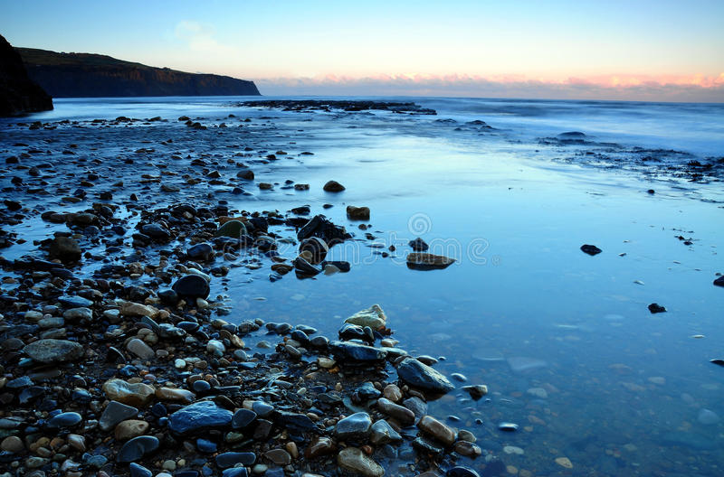 Boggle hole North Yorkshire coast England. Rocks and pebbles with evening tide coming in stock image