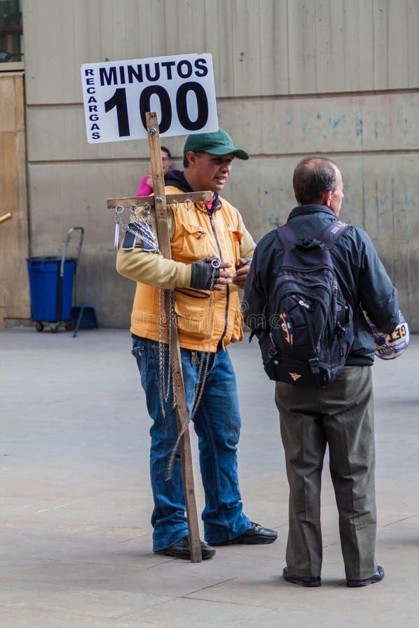 BOGOTA, COLOMBIA - SEPTEMBER 24, 2015: De telefoon van mensenaanbiedingen verzoekt de stad in 100 peso's binnen van Bogot stock afbeelding