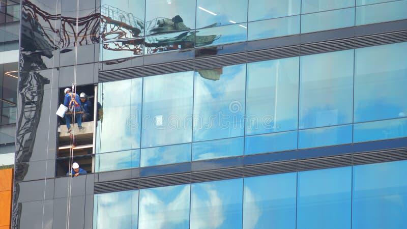 Bogota Cundinamarca/Colombia - April 8 2016: Arbetare som gör ren de glass fönstren av en modern byggnad med reflexionshimmel arkivfoton