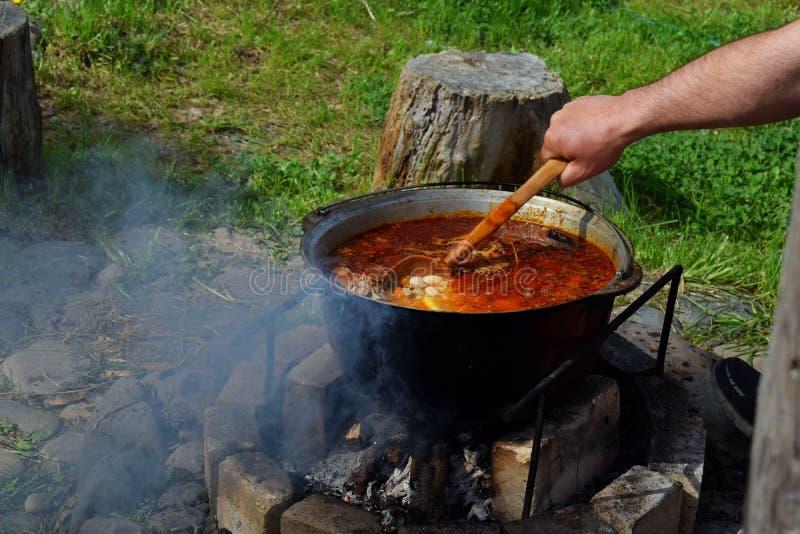 Bograch Soep met paprika, vlees, boon, groente, bol Traditionele Hongaarse Goelasj in ketel Maaltijd in openlucht op wordt gekook royalty-vrije stock afbeeldingen