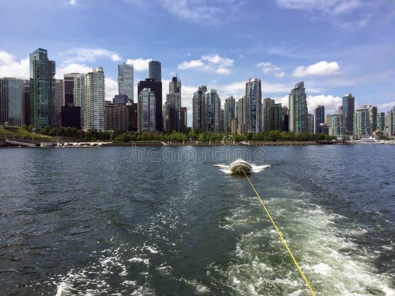 Bogsera ett litet fartyg eller en jolle på en sommardag med horisontnollan royaltyfri fotografi