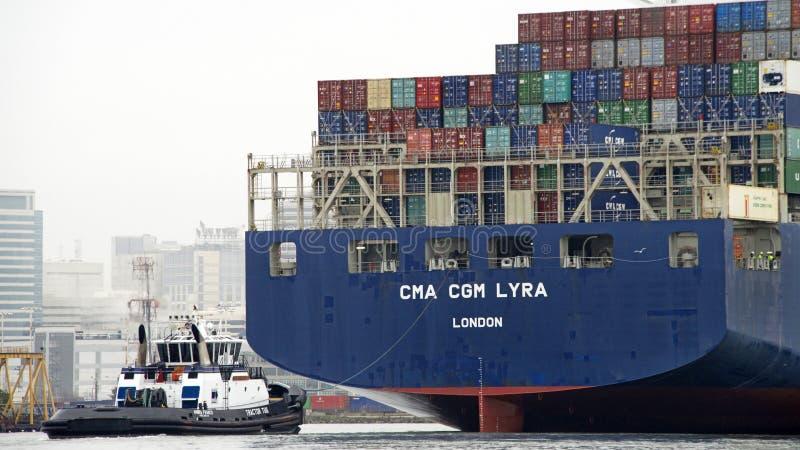 Bogserbåt ABRAH FRANCO som hjälper CMA CGM-LYRA för att manövrera royaltyfri foto