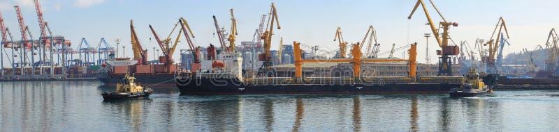 Bogserbåt på pilbågen av lastfartyget som hjälper skytteln för att manövrera i havsport arkivfoto