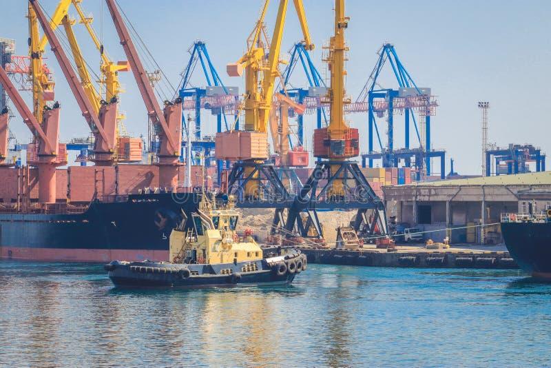 Bogserbåt på pilbågen av lastfartyget som hjälper skytteln för att manövrera i havsport royaltyfri bild