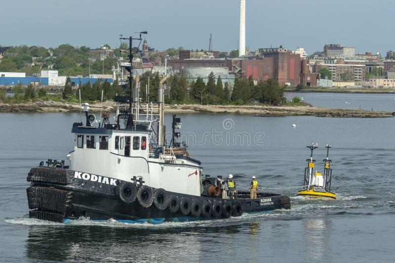 Bogserbåt som bogserar Lidar-bojet ut ur den New Bedford hamnen royaltyfria foton