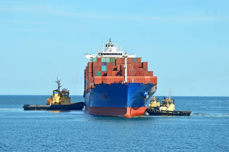 Bogserbåt som hjälper behållarelastfartyg royaltyfri foto