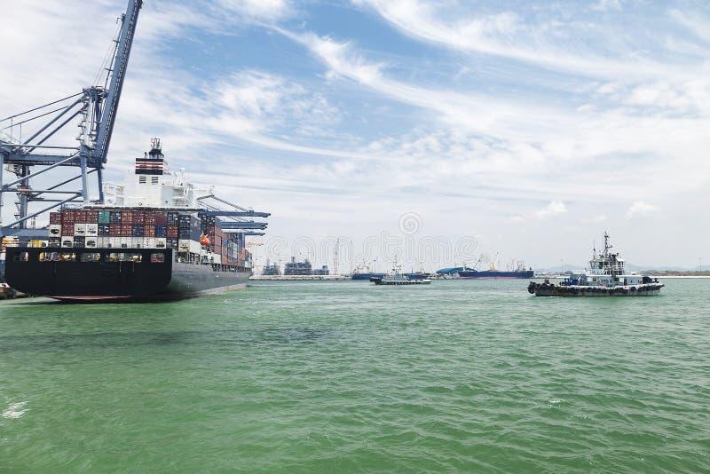Bogserbåt som hjälper behållarelastfartyg royaltyfri bild