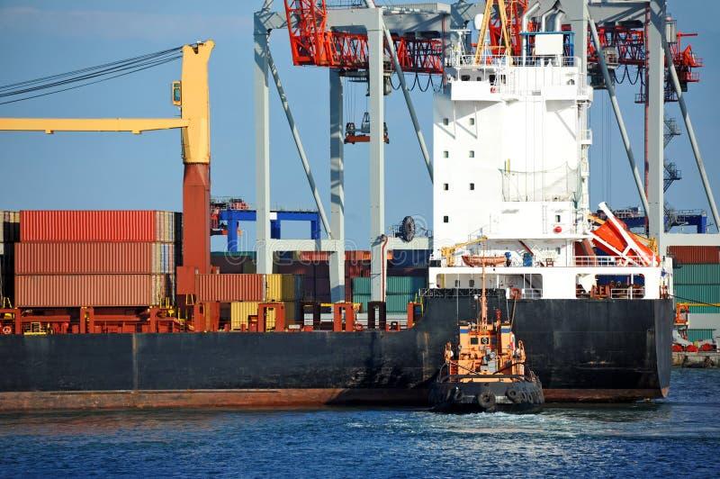 Bogserbåt som hjälper behållarelastfartyget arkivfoton