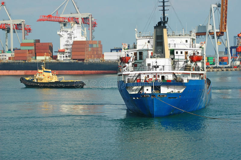 Bogserbåt som hjälper det bulk lastfartyg royaltyfri bild