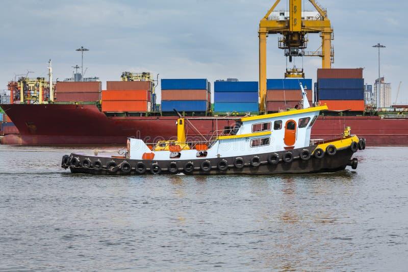 bogserbåt som hjälper lastfartyget i stora partier för att härbärgera frakter arkivfoto