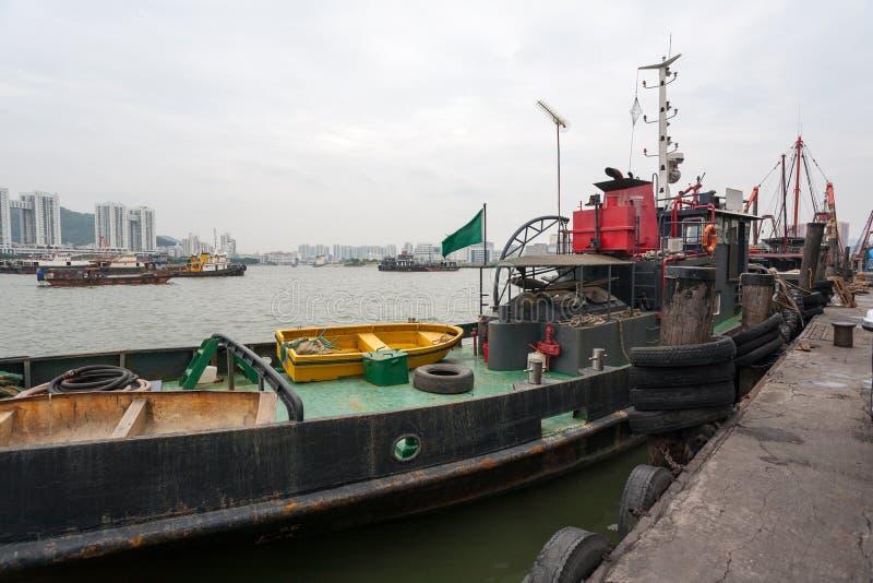Bogserbåten och fiskeskyttlar är på hytten i porten av Macao. arkivbilder