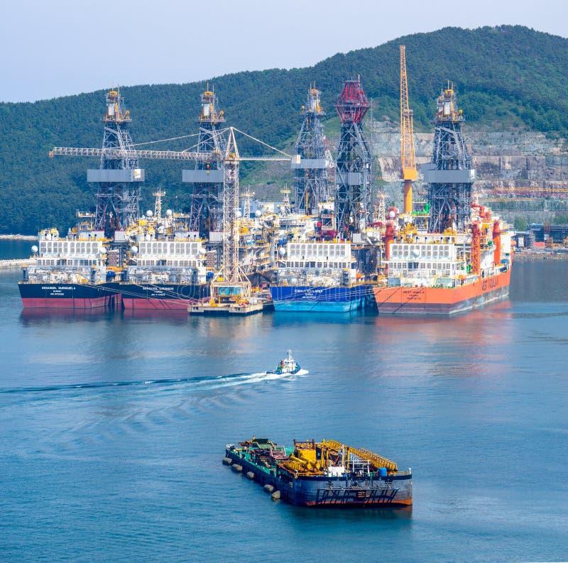 Bogserbåten seglar passerandedriilskepp i fjärden av Daewoo skeppsbyggeri och Marine Engineering DSME i den Okpo staden, Sydkorea arkivbilder