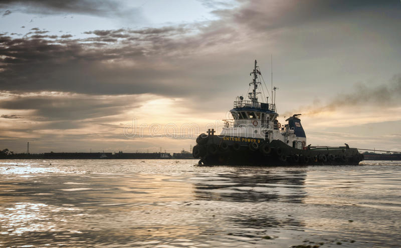 Bogserbåtfartyg i floden under solnedgång royaltyfri foto