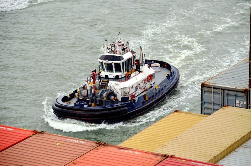 Bogserbåtfartyg som hjälper till behållareskeppet royaltyfria bilder