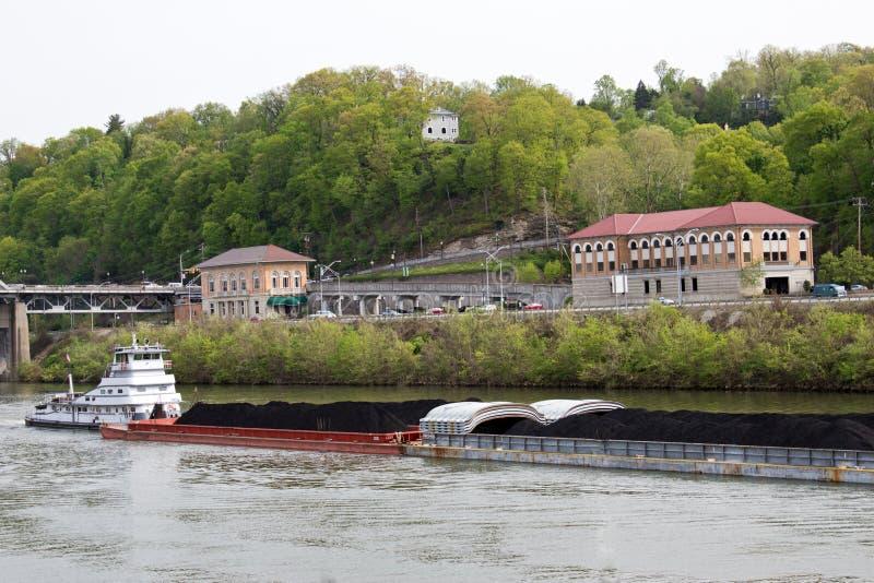 Bogserbåtflyttningpråm som fylls med kol arkivfoto