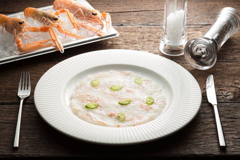 Bogt das carpaccio aus, das mit Paprika, Langoustines auf einer weißen Platte und hölzerner rustikaler brauner Tabelle mit Abende stockfotografie
