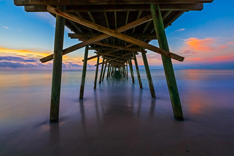 Bogue Inlet Pier at Daybreak. The rising sun paints the sky over the sea with vivid colors as seen from beneath the Bogue Inlet Fishing Pier in Emerald Isle stock image