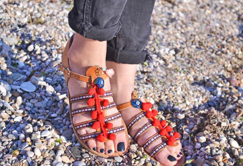 Bohemian sandals advertisement on the beach - greek leather sandals stock photos