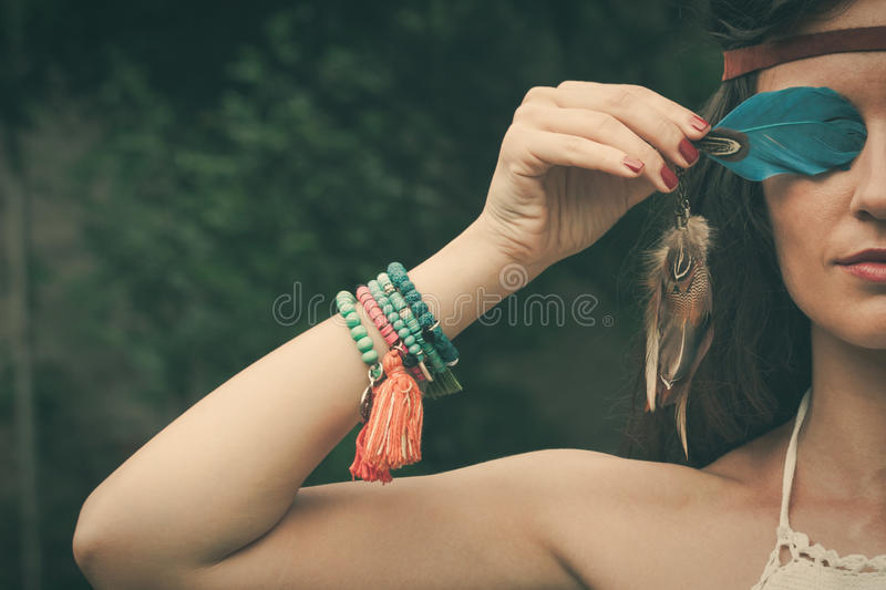 Bohemian style girl portrait. Young bohemian fashion style woman with feather portrait closeup royalty free stock photos