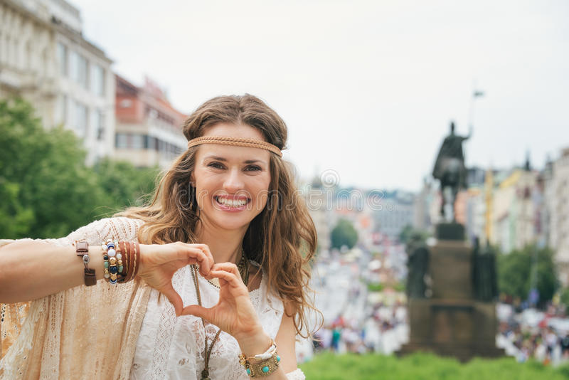 Bohemian woman tourist in Prague showing heart shaped hands. Brunette bohemian woman tourist standing on Wenceslas Square in Prague and showing heart shaped royalty free stock photography