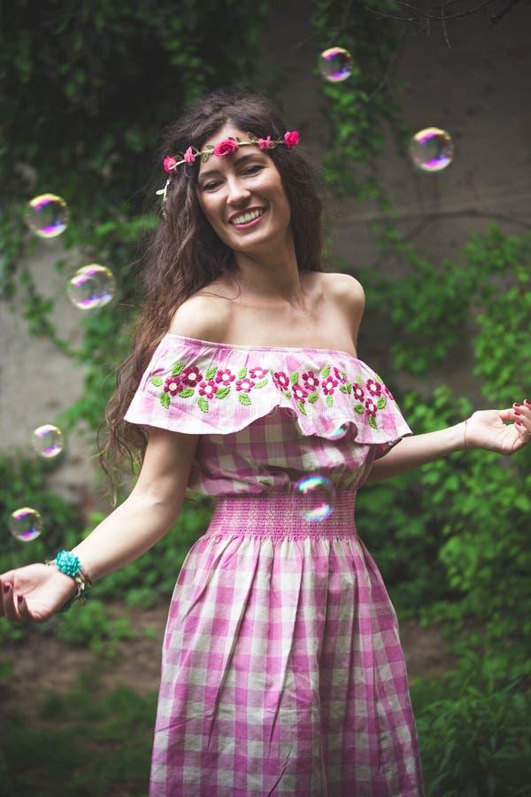 Bohemisk flickalek med såpbubblor i trädgård arkivbild