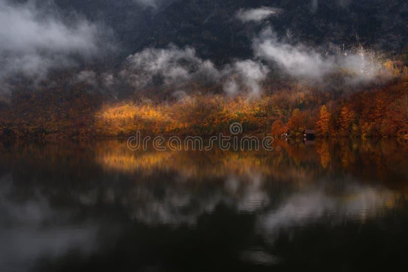 Bohinj-sjön, Slovenien Idylliskt regnlandskap med reflektion av höstskogen för rödböna, bergsområden, fiskarnas hus och arkivfoto