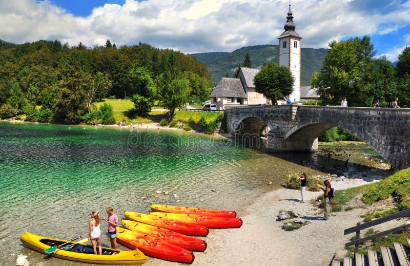 Bohinjmeer met boten en toeristen, Kerk van St John Doopsgezind met brug Triglav Nationaal Park, Slovenië stock fotografie
